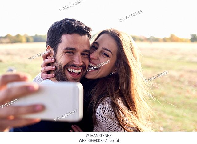 Happy couple taking a selfie in a park