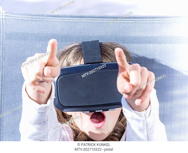 Girl cheering while wearing virtual reality glasses