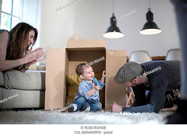 Parents playing with baby boy and cardboard box