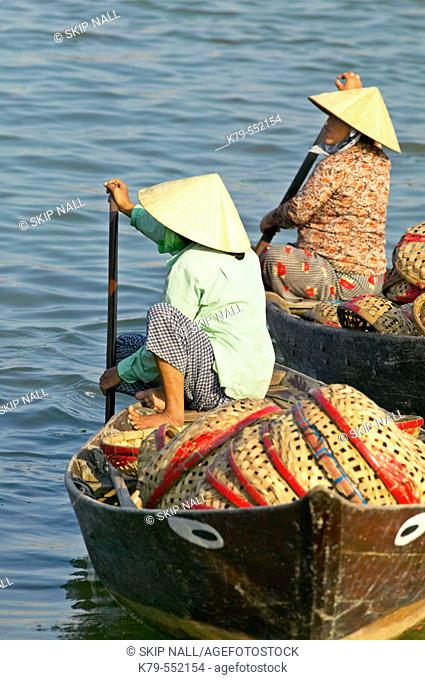 Women with baskets wait in boats on the river at the market in Hoi An