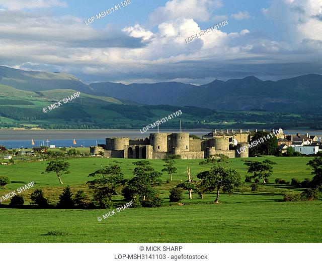 Wales, Anglesey, Beaumaris. A general view of Edward I's Beaumaris Castle looking south to the Menai Strait and the mountains of Snowdonia