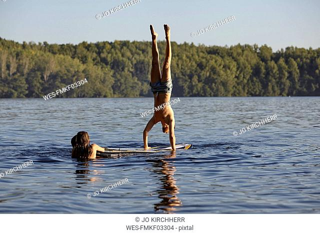 Man doing a handstand on a paddleboard in a lake