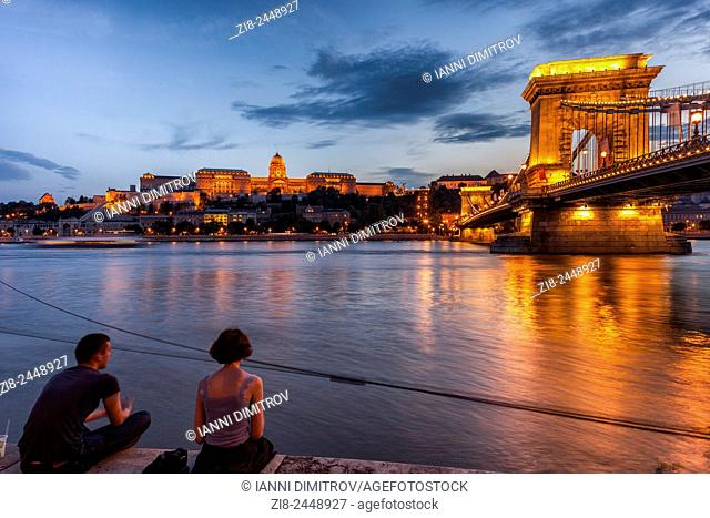 Young couple on the banks ov river Danube,Buda Castle and Szechenyi Chain Bridge at night,Budapest Hungary