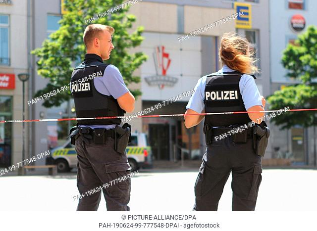 24 June 2019, Saxony-Anhalt, Halberstadt: Policemen are standing near the town hall passage at a barrier tape. After a bomb threat in the city centre of...