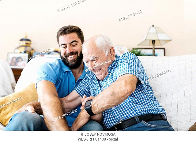 Adult grandson and his grandfather sitting on the couch at home tickling each other