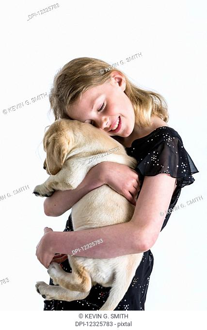 A smiling young girl hugs a Labrador puppy against a white background; Anchorage, Alaska, United States of America