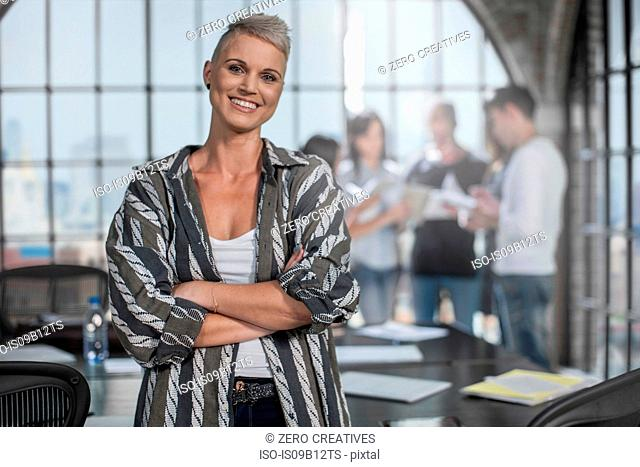 Smiling woman with colleagues discussing in background