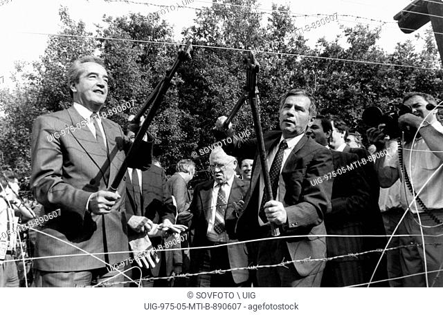 Austrian Foreign Minister Alois Mock (left) and his Hungarian counterpart Gyula Horn cut the barbed wire in the region of Sopron
