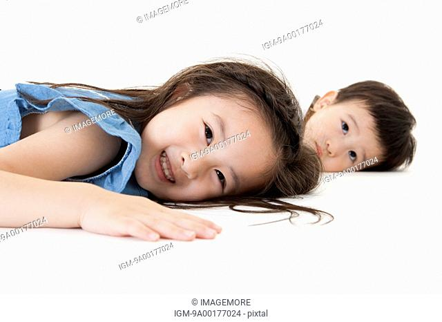 Girl and baby boy lying down with smile