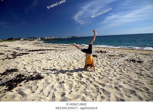 France, Bretagne, Finistere, Trevignon, Girl doing cartwheel on beach