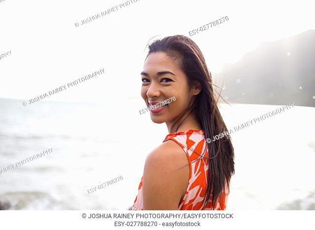 Lifestyle portrait of an attractive Hawaiian woman wearing a flower dress at Kahana Bay on Oahu Hawaii