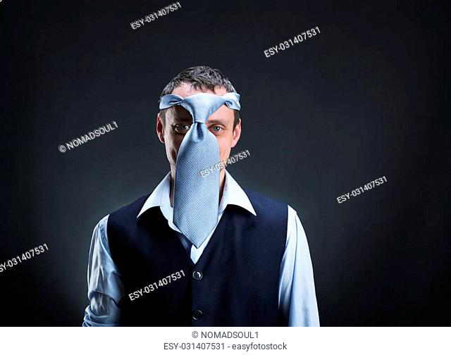 Strange man with necktie on his head over grey