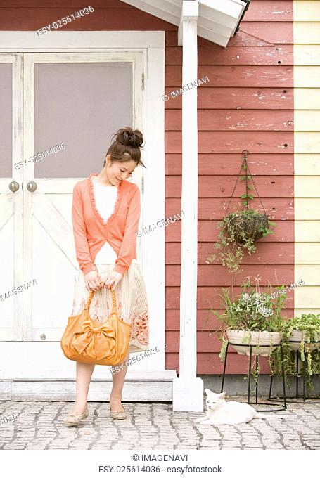 Young woman and cat at front door