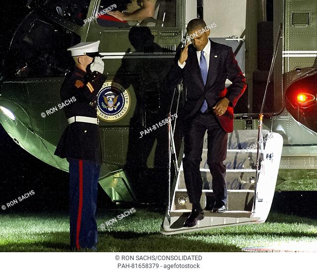 United States President Barack Obama salutes the Marine Guard as he arrives on the South Lawn of the White House in Washington, DC following his trip to Ottawa