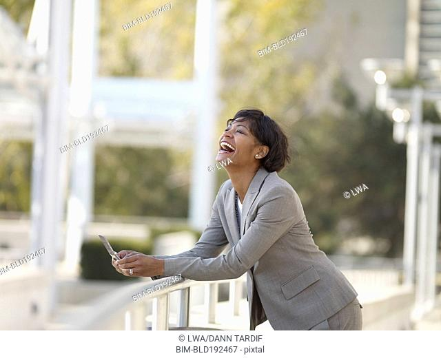 African businesswoman laughing and holding cell phone