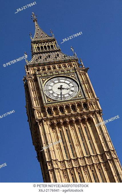 Looking up at Big Ben and clock against blue sky