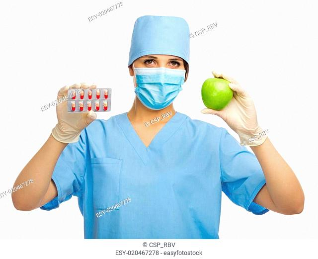 Young doctor with apple and pills