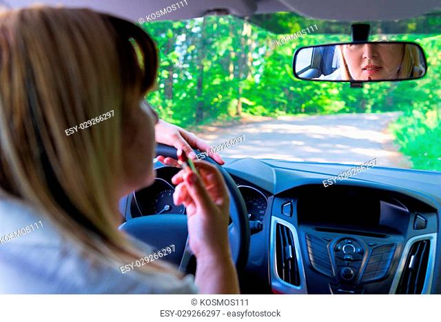 mature woman paints her lips while driving
