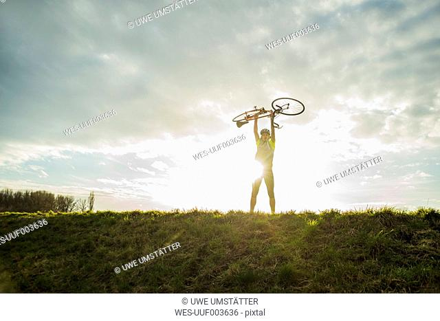 Germany, Mannheim, young man cheering with bicycle
