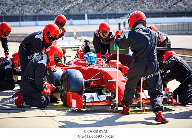 Pit crew working on formula one race car in pit lane