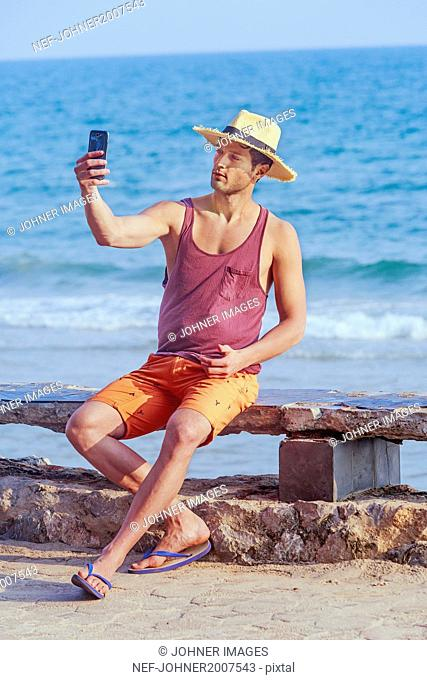 Young man on beach taking selfie