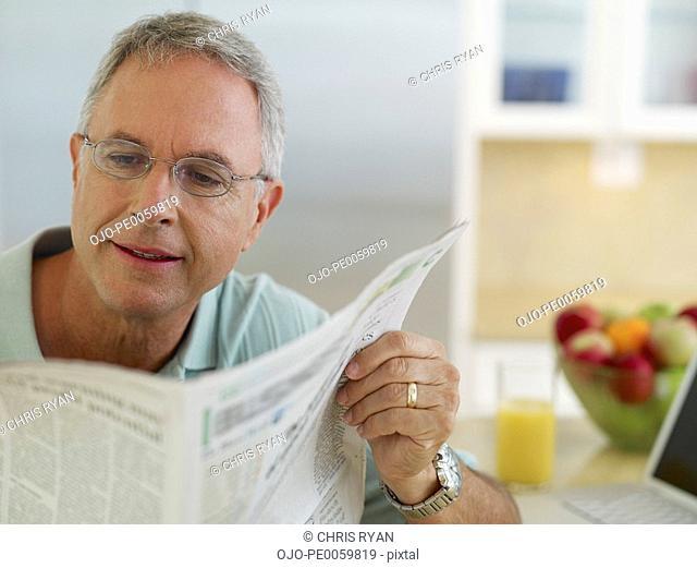 Man in kitchen reading newspaper