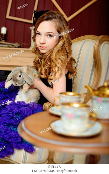 Young girl in blue skirt at the image of Alice in Wonderland