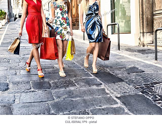 Neck down view of three fashionable young women shoppers, Cagliari, Sardinia, Italy
