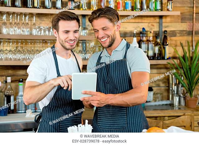 Smiling waiters using digital tablet at counter