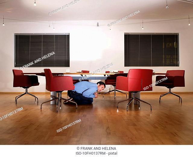 Man hiding under boardroom table