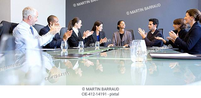 Business people applauding colleague in meeting