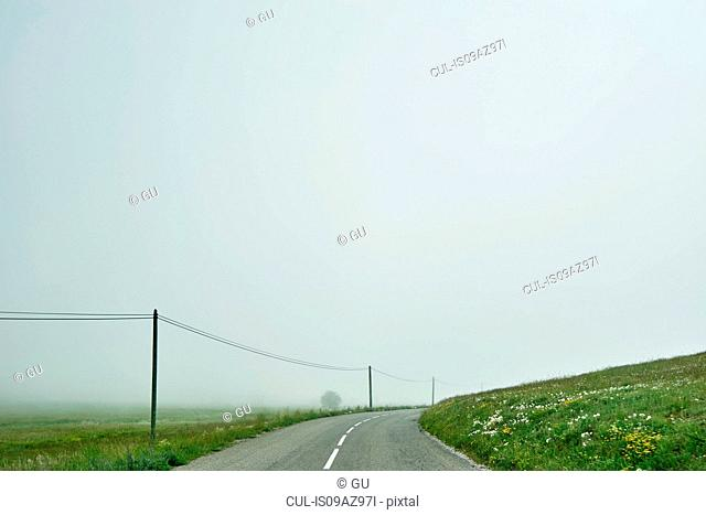 Landscape and empty rural road in mist, Gourdon, Alpes Maritimes, France
