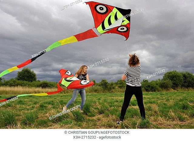 two teen girls flying a kite, Centre-Val de Loire region, France, Europe