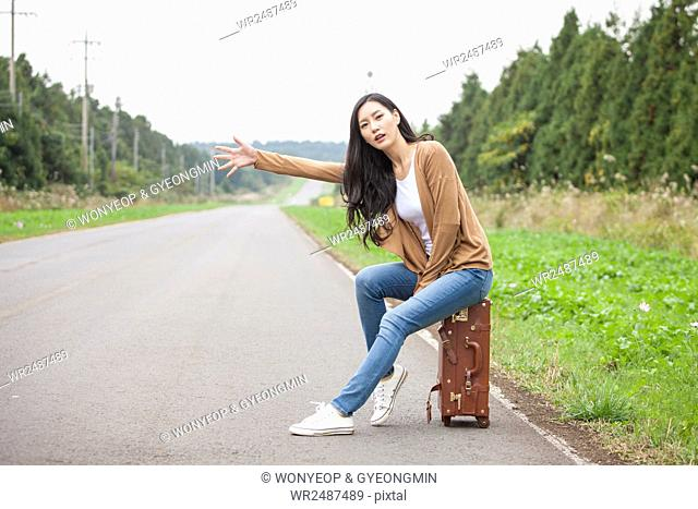 Young woman sitting on a carrier and trying to hitch a ride on a road