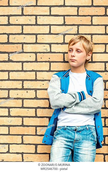 Portrait of a boy on a background of a brick wall