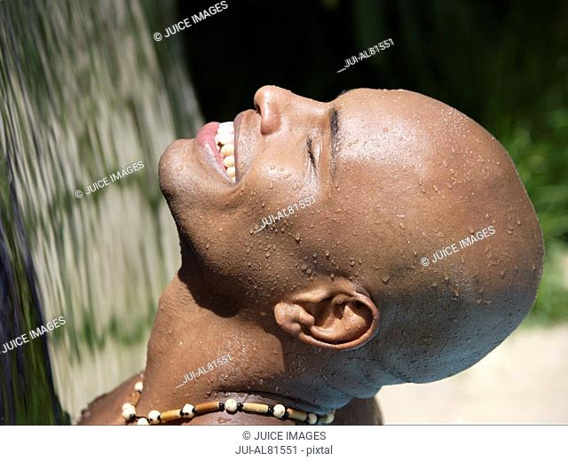 African man with face up to sunlight smiling
