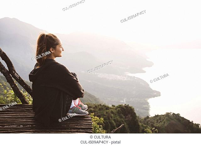 Young woman on balcony looking out over Lake Atitlan, Guatemala