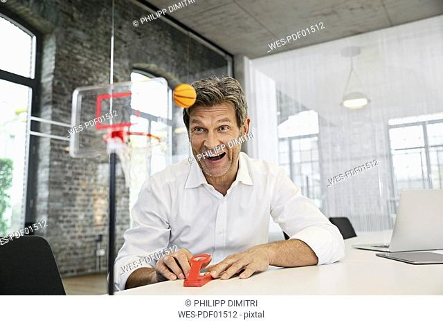 Happy businessman playing mini basketball game in modern office