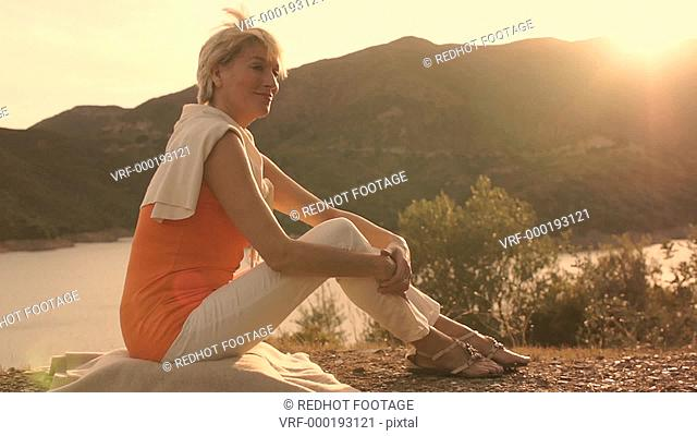 Dolly shot of woman sitting relaxing overlooking lake in sunset