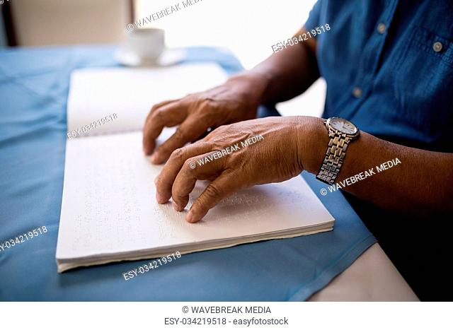 Midsection of senior man reading braille book at table