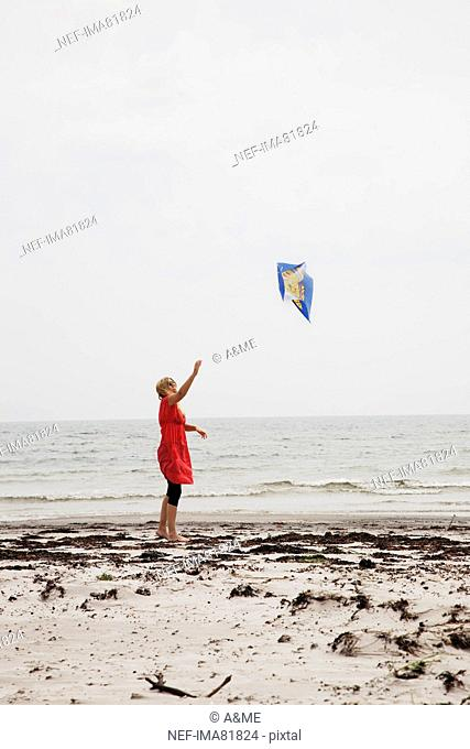 Woman flying kite at beach