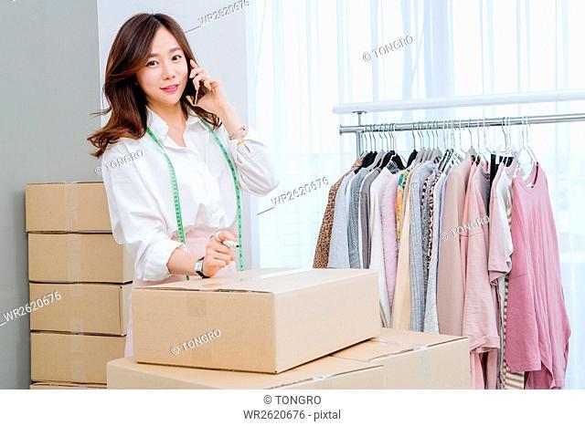 Female fashion designer talking on cellphone