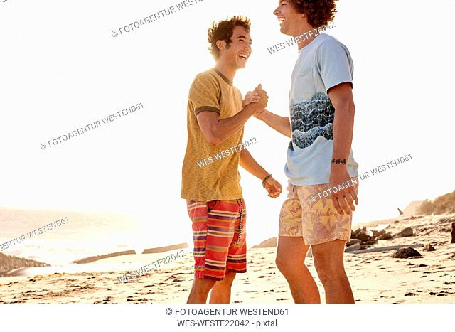 Two happy young man on the beach