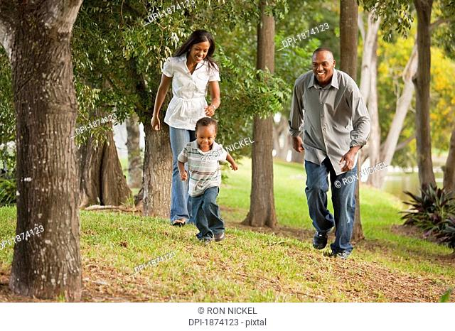 fort lauderdale, florida, united states of america, a father and mother chasing their young son through a park