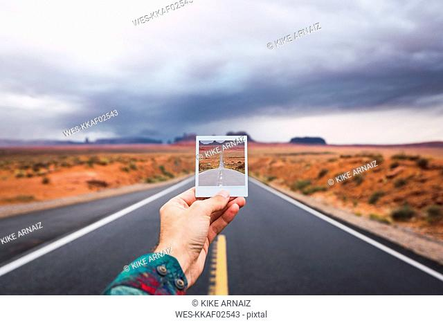 USA, Utah, Hand holding instanf foto over road to Monument Valley