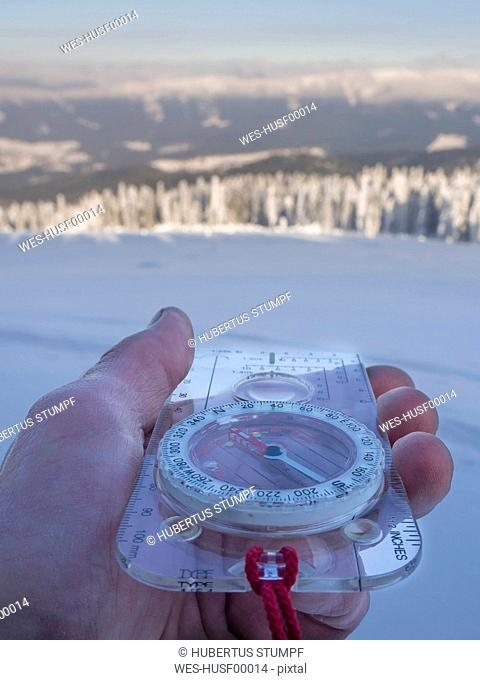 Germany, Upper Bavarian Forest Nature Park, man's hand holding compass in winter