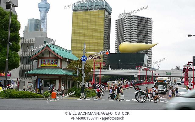 Tokyo Japan with golden horn of Kirin Beer with locals on street in Asakusa District and traffic with Tokyo Skytree in background