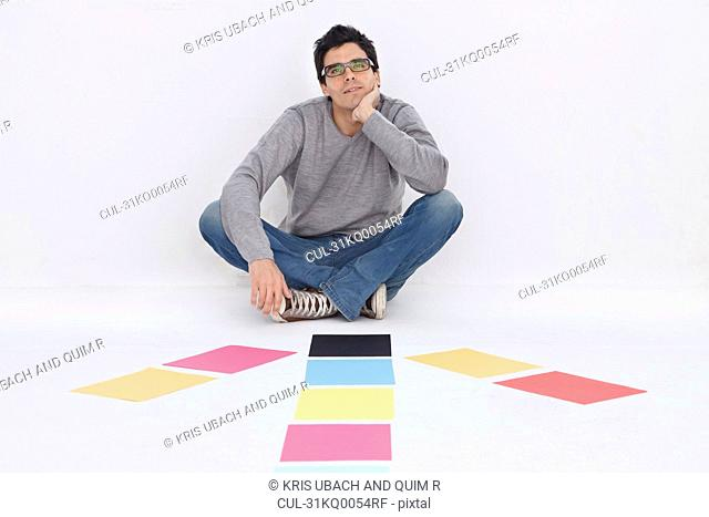 Man sitting with coloured paper, smiling