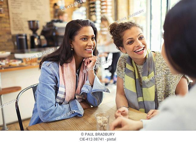 Smiling women friends talking at cafe table