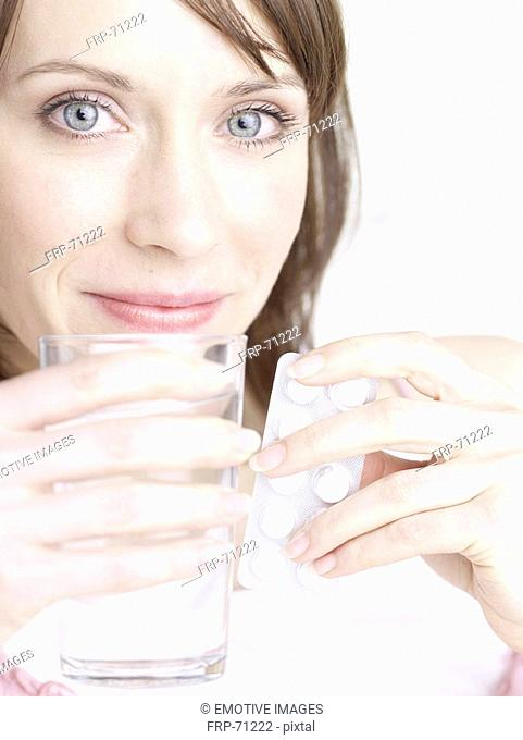 Woman with glass of water and pills